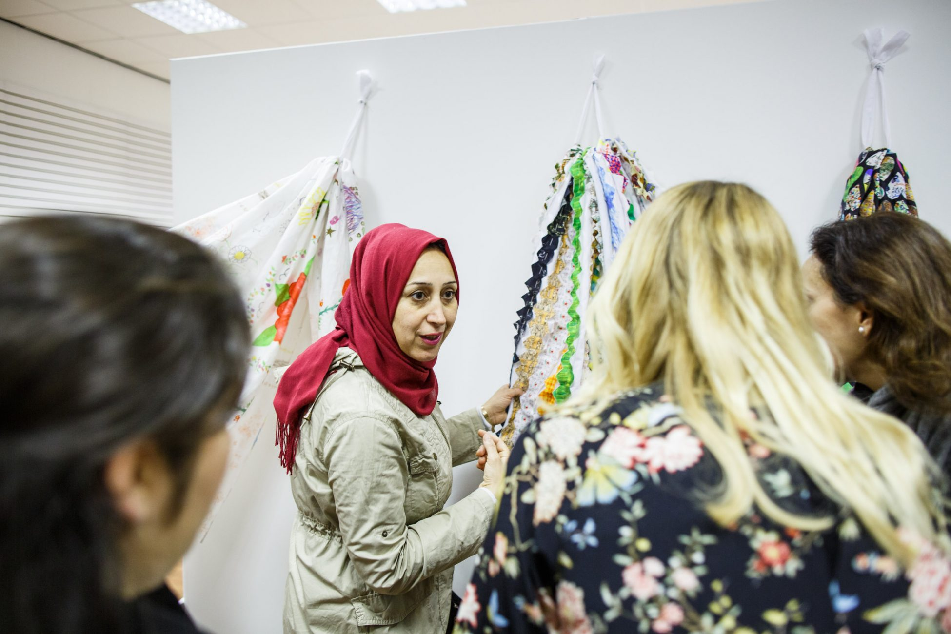 Photo of a gallery showing three sets of colourfully decorated fabric hanging down against a white wall. A woman wearing a beige coat and red hijab is holding one of the pieces of fabric and talking to another group of women as if talking about the fabric.