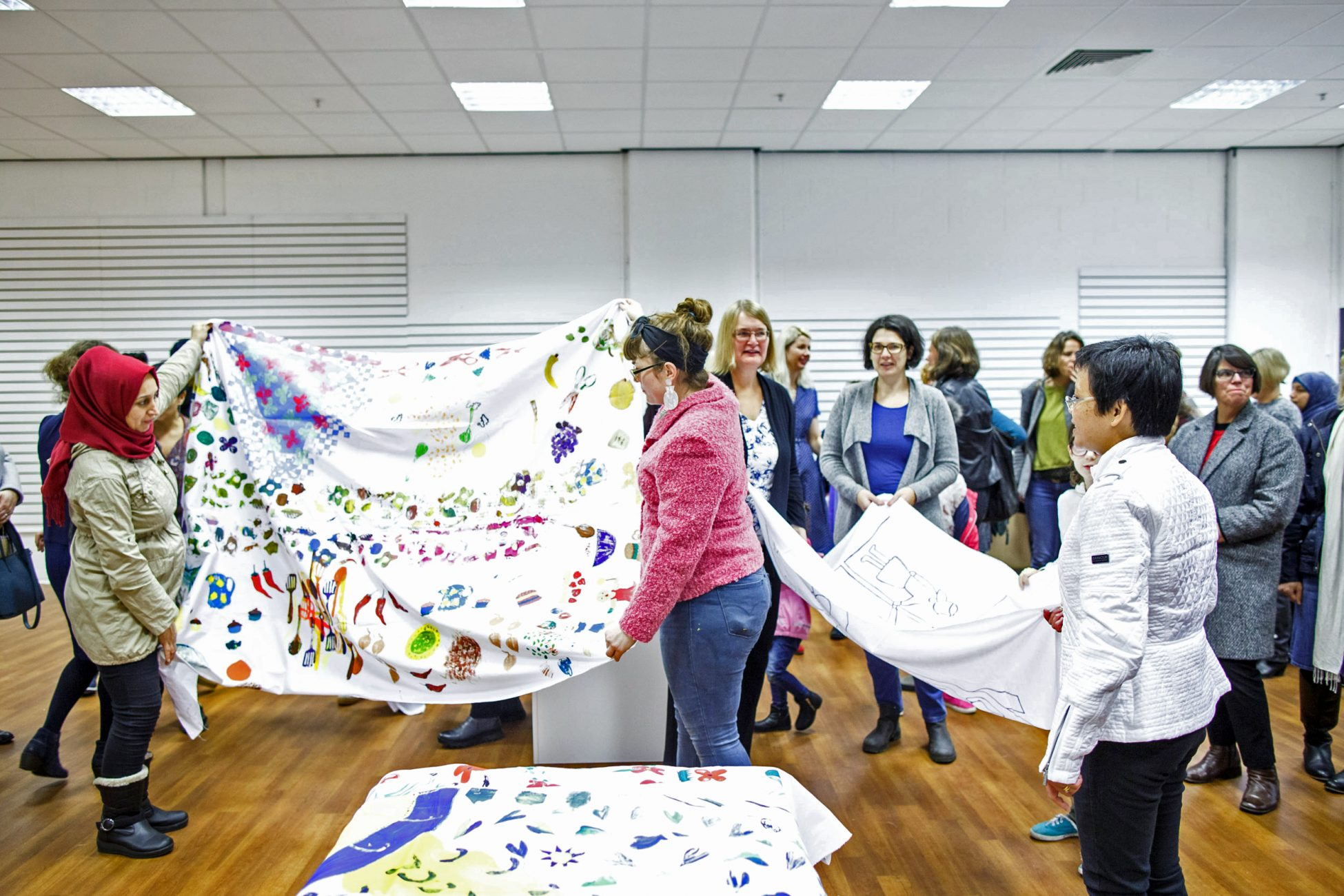 Photo of a group of women in a gallery, A decorated piece of fabric is spread over a table in the front, behind that some of the women are holding up two more large pieces of fabric that have been decorated. Others are milling around the gallery space.