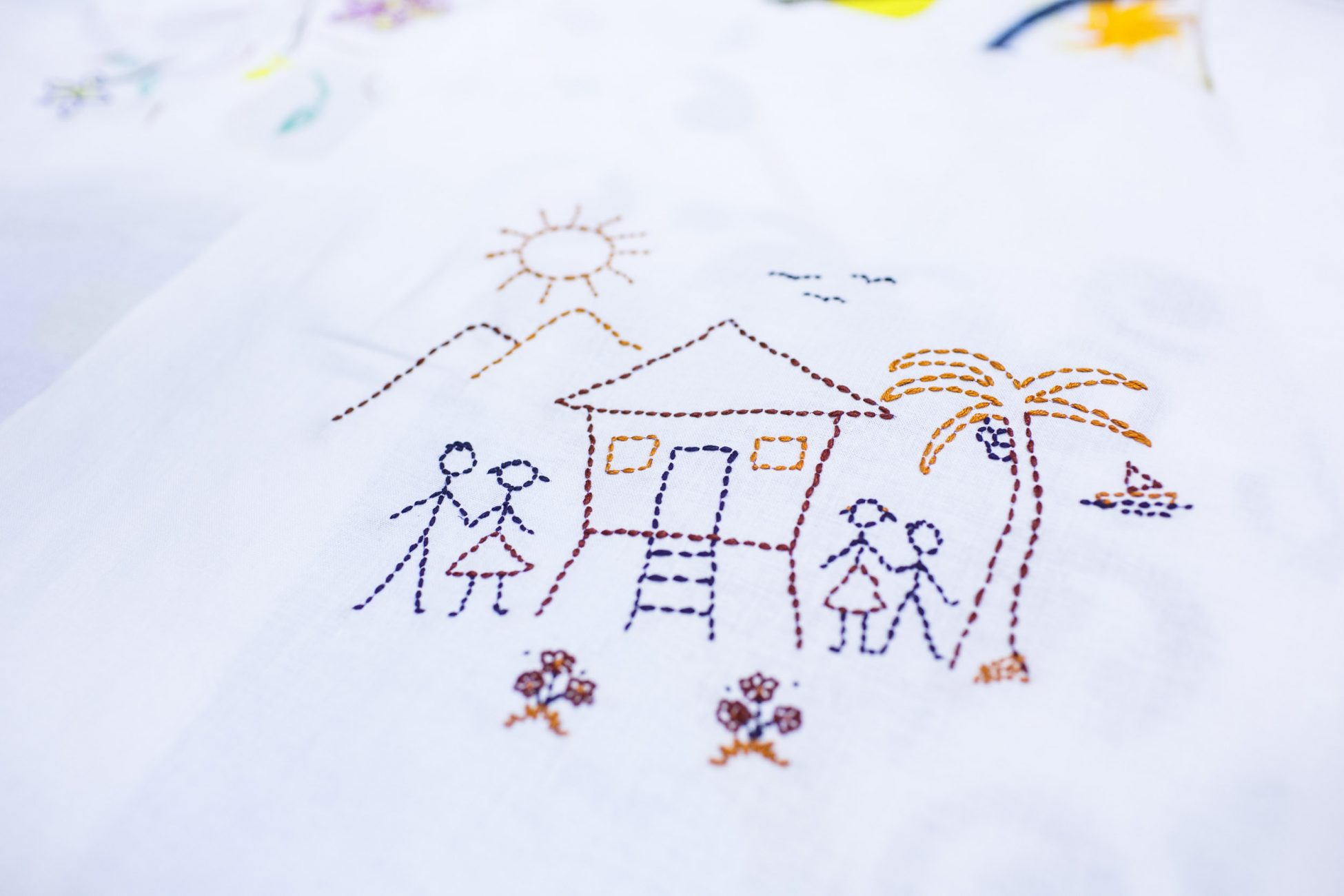 Photo of a piece of white fabric with an embroidery depicting four stick figures, a house raised up on stilts, a palm tree, mountains, birds, flowers and the sun.