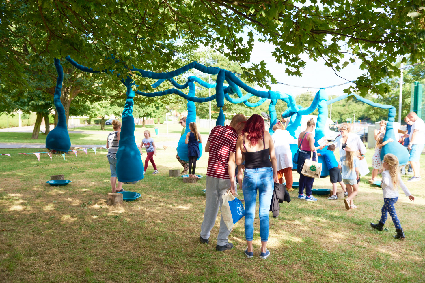 A photo showing an art installation on a green in front of a row of houses. The installation is large blue fabric tubes strung up about 2.5 metres in the air, with sections hanging down into large lumpy bulbs just off the ground. Approximately 20 people are walking around the space, looking at, touching and hugging the bulbs, and chatting to each other.