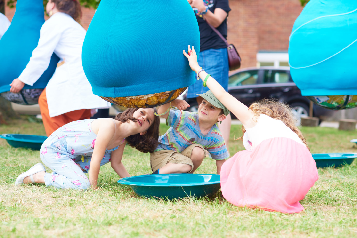 A photo showing an art installation on a green in front of a row of houses. The installation is large blue fabric tubes strung up about 2.5 metres in the air, with sections hanging down into large lumpy bulbs just off the ground. Three children are crouched on the ground looking up into the bottom of one of the bulbs, which has netting at the bottom showing that it is full of jumbled up fabrics and/or clothes. Underneath is a large blue enamel dish.