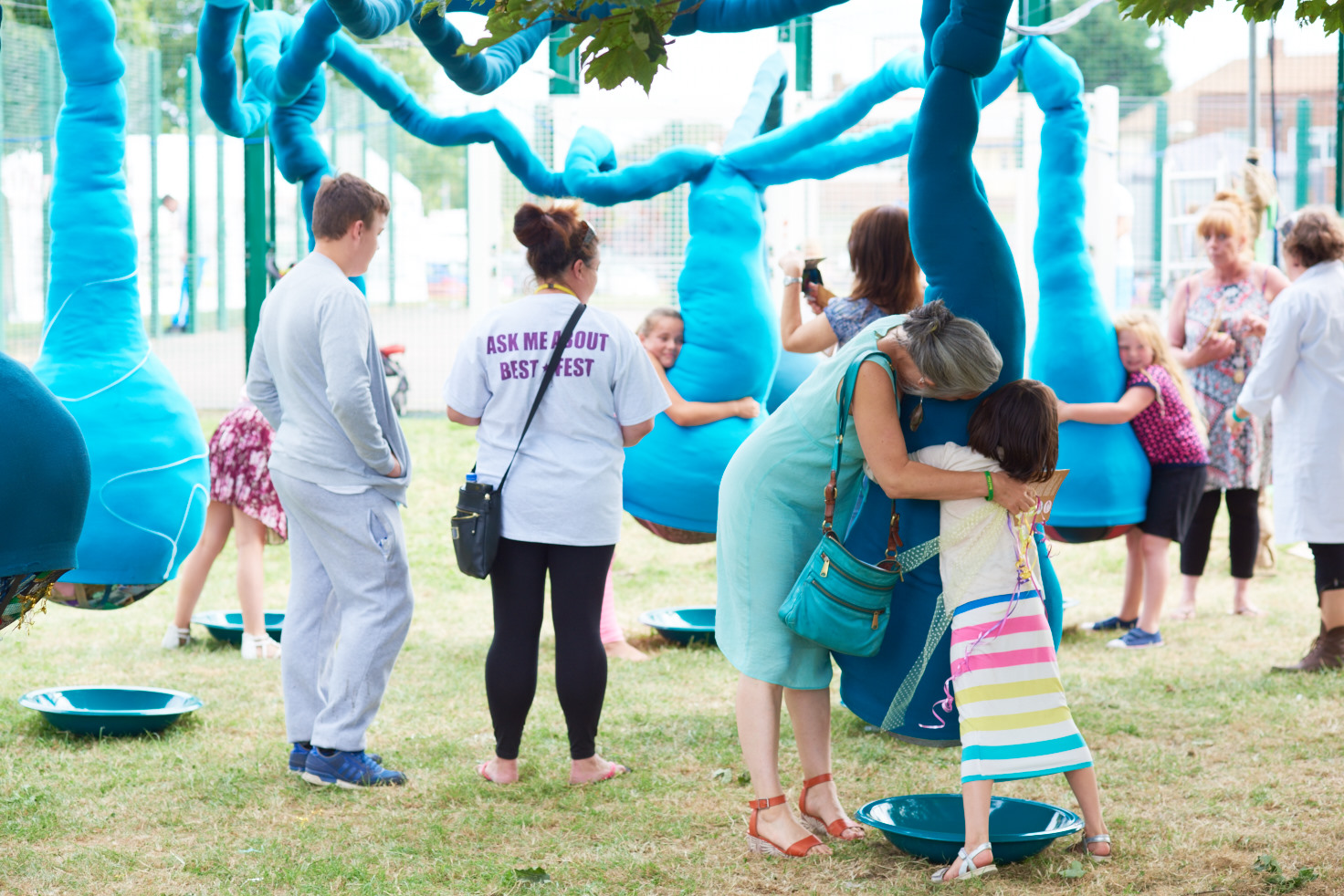 A photo of a playing field with a large art installation. The installation consists of various large blue fabric bulbs hanging down from a network of blue fabric tubes which are strung up in the air using wires attached to nearby trees. About 10 people are grouped around the hanging bulbs, some holding or touching them.