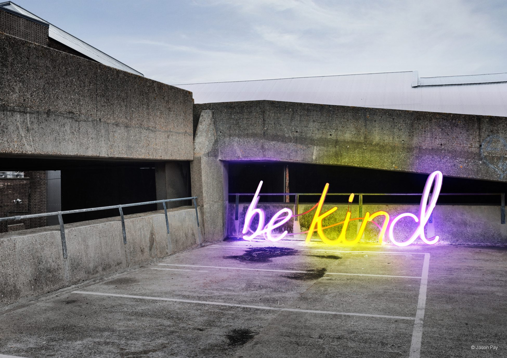 A photo of the upper level of a concrete car park with a large neon sign spelling out