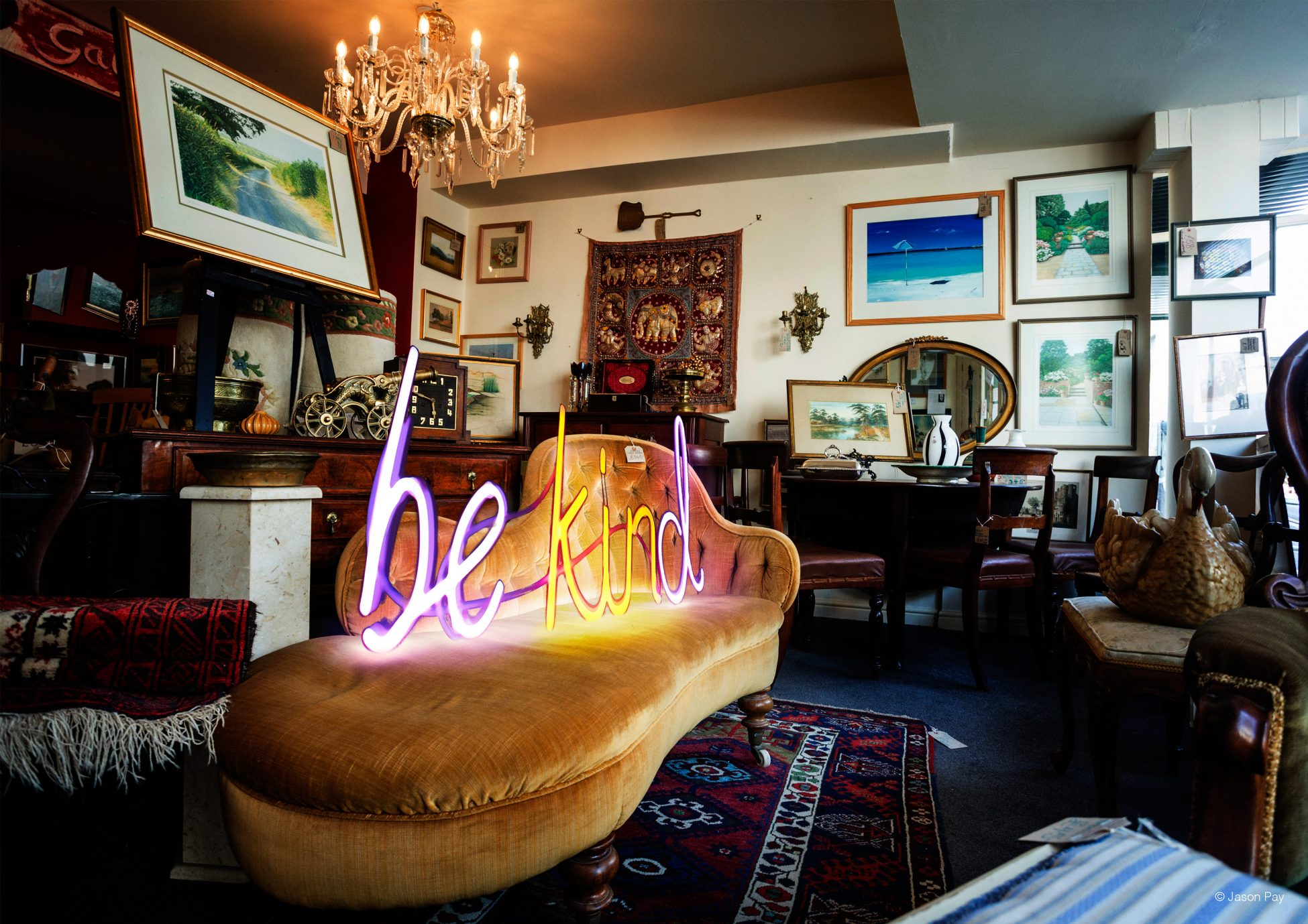 Digital artwork showing a photo of a room with various chairs, rugs, framed paintings, pieces of furniture and lights. On a yellow chaise longue in the centre of the room is a neon sign spelling out the words 'be kind' in pink and yellow light.