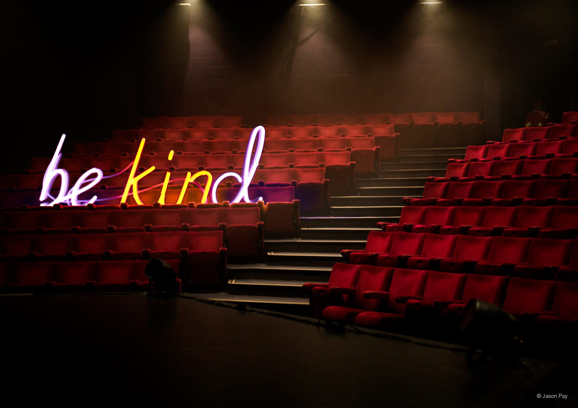 Digital artwork of a photo taken from a stage looking out over tiered rows of red theatre seats. Along one row is a giant neon sign spelling out 'be kind' in pink and yellow light.