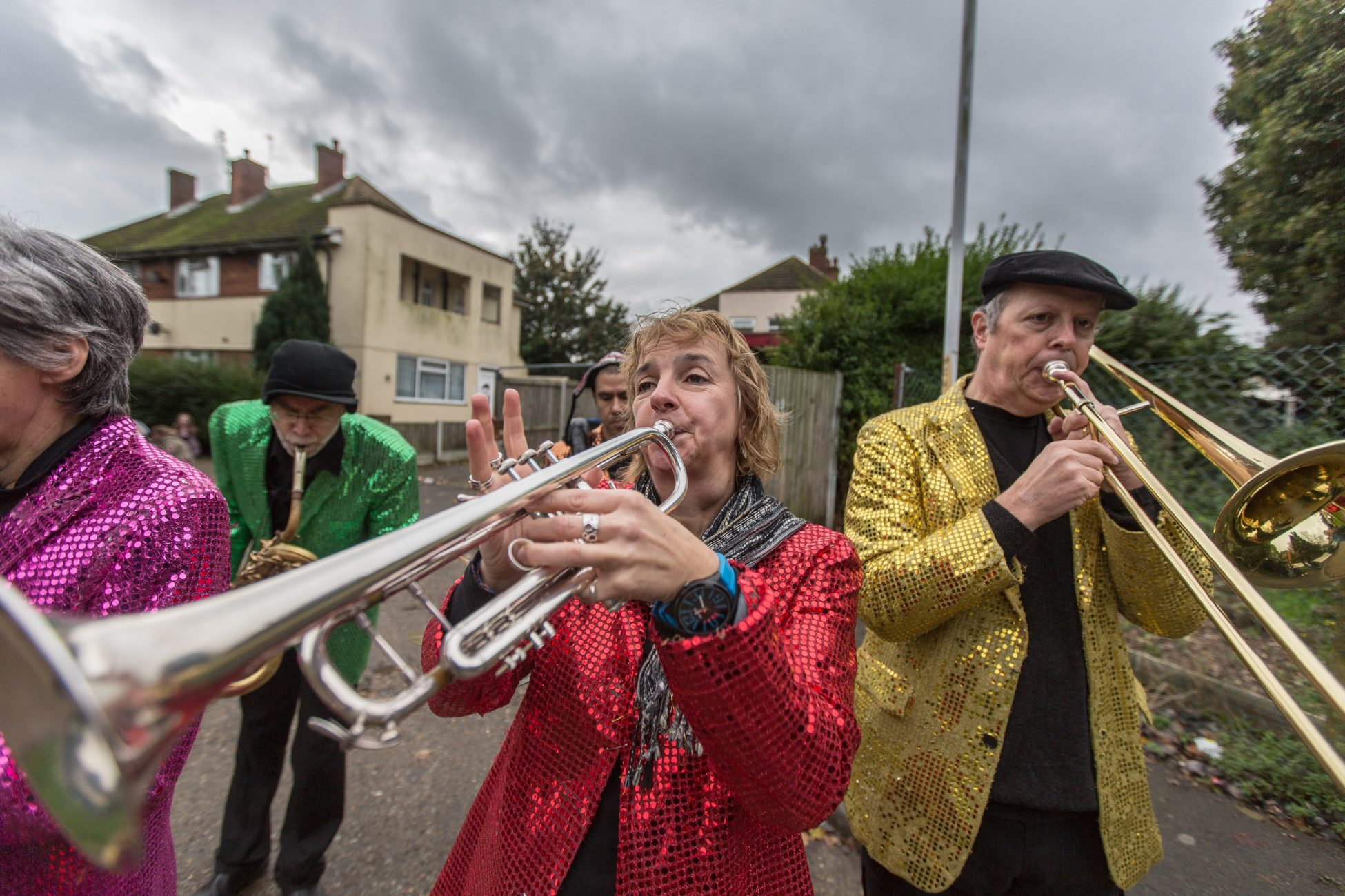 A photo of four people standing in a residential street and wearing bright sequin jackets, one pink, one gree, one red and one gold. They are each playing a different brass instrument.