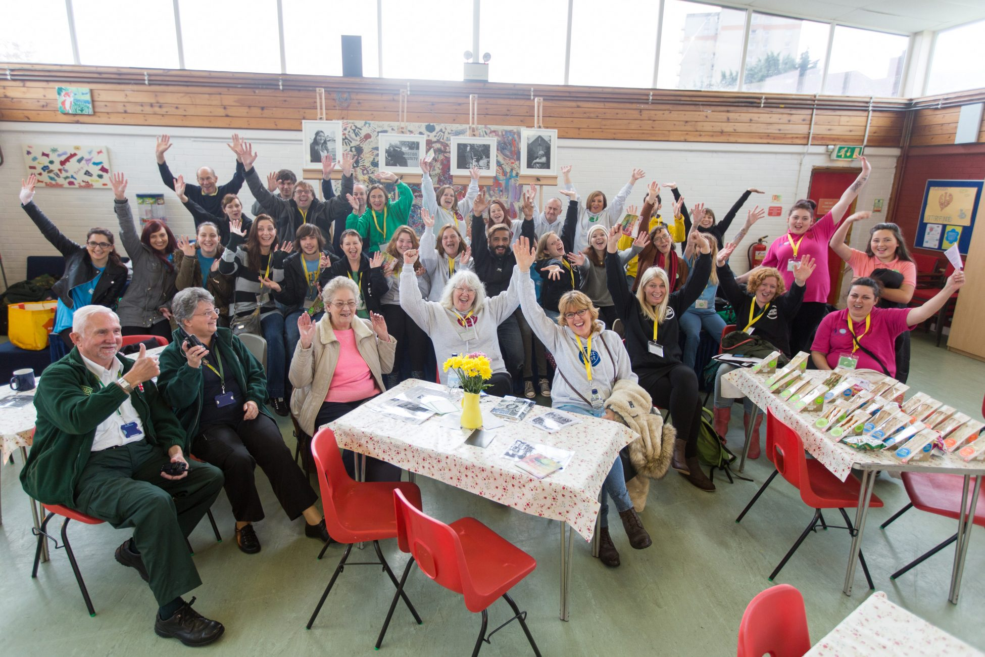 Photo of a group of about 30 people in a hall or community centre with various tables and chairs with flowers and sandwiches on them. The people are all facing the camera and cheering with his arms in the air.