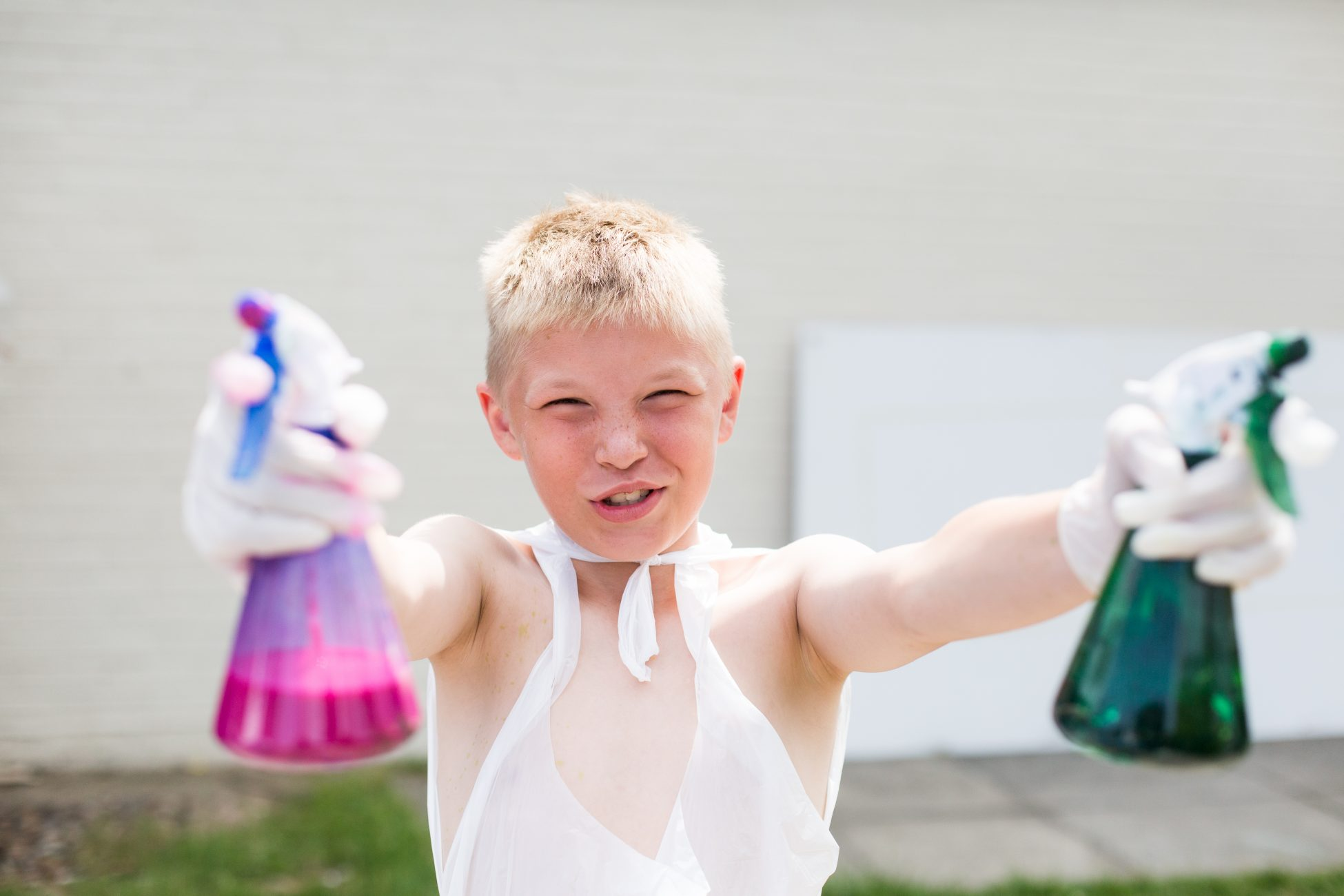 Photo of a child wearing a plastic apron and rubber gloves holding 2 spray bottles full of paint/dye up to the camera