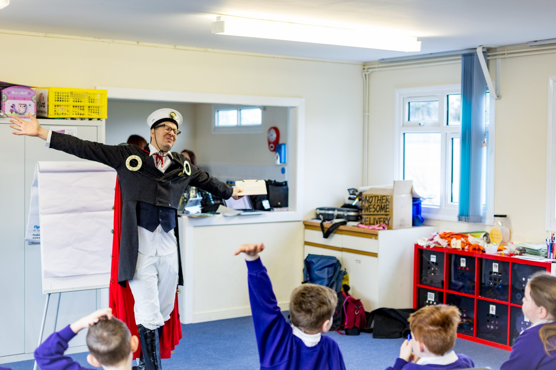 Photo of Steampunk Bob standing in front of a group of school children with his arms stretched out to the sides. One of the children has their hand raised.
