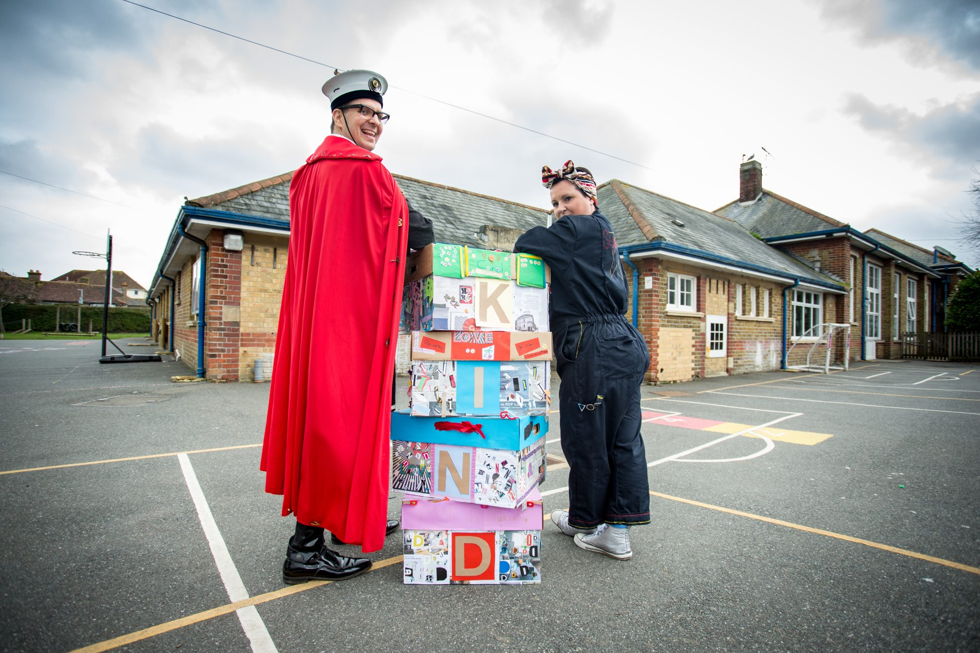 Photo of steampunk bob and nova marshall standing in a school playground. Between them is a stack of four colourfully decorated cardboard boxes each with a letter on the side so that they spell out the word KIND