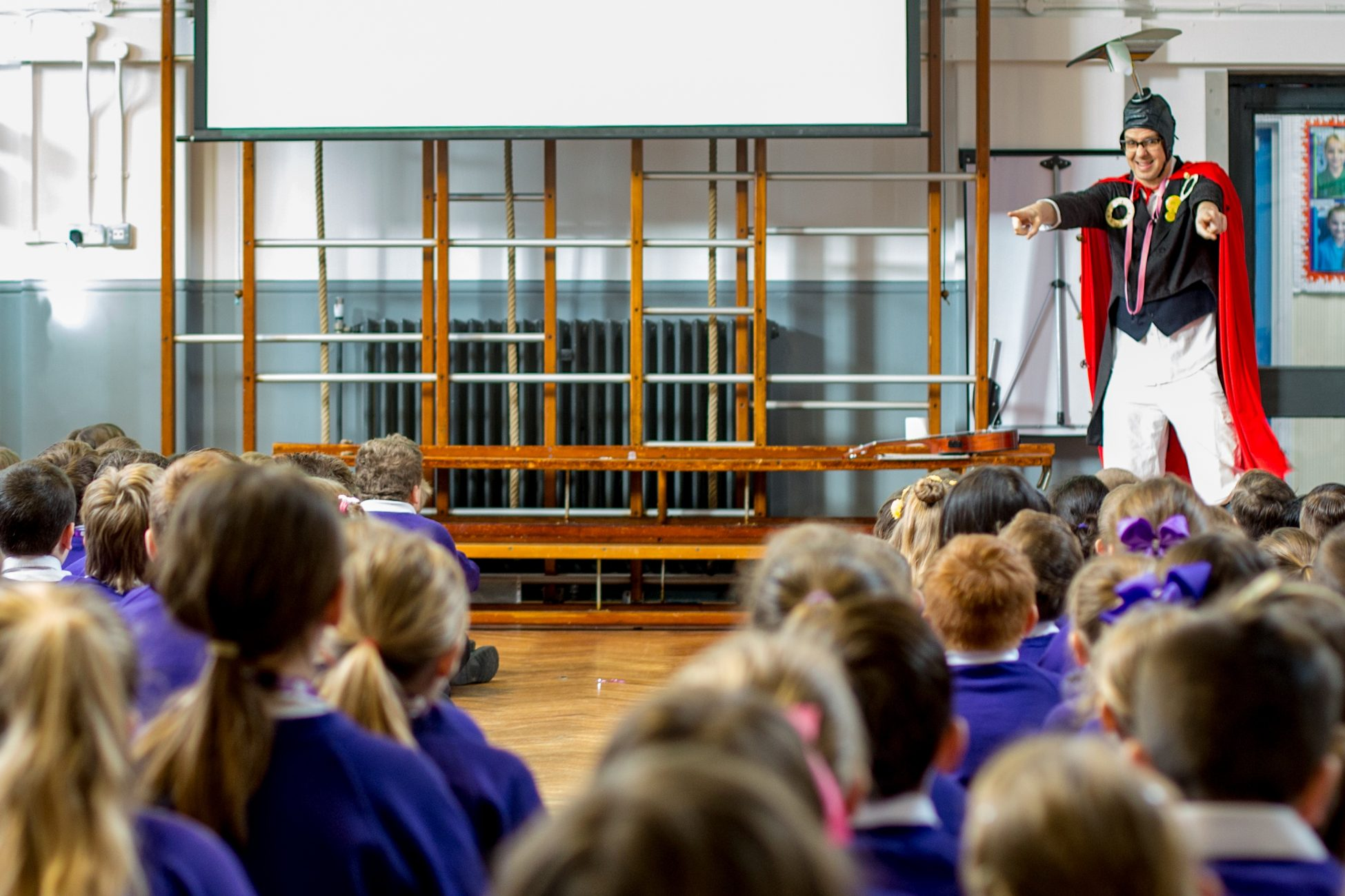 Photo of steampunk bob standing in front of a large group of school children sitting on the floor of a school hall. Bob is smiling and pointing at the children with both hands.
