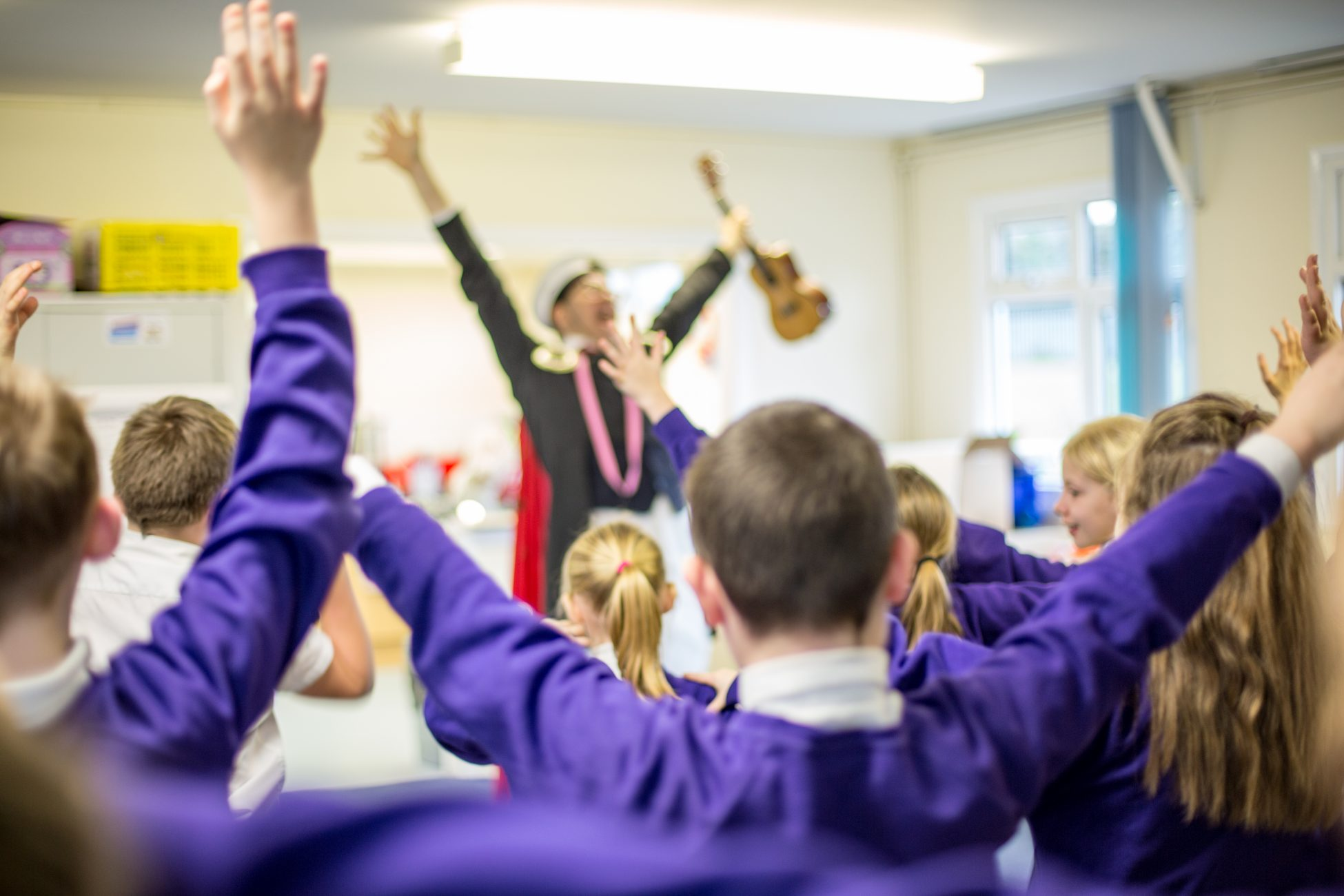 Photo showing a blurry man in a classroom holding a ukelele with his arms raised over his head. A group of children facing him are copying his movements.