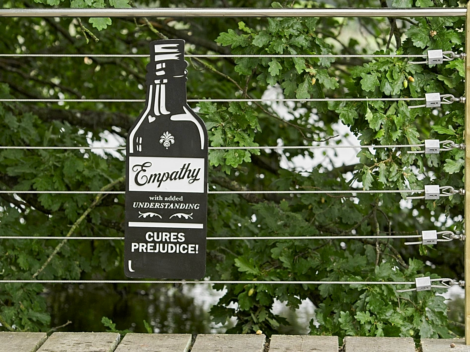 A wooden walkway next to trees and bushes. With a wire and wooden fence along the edge. Attached to the wires is a bottle-shaped sign saying