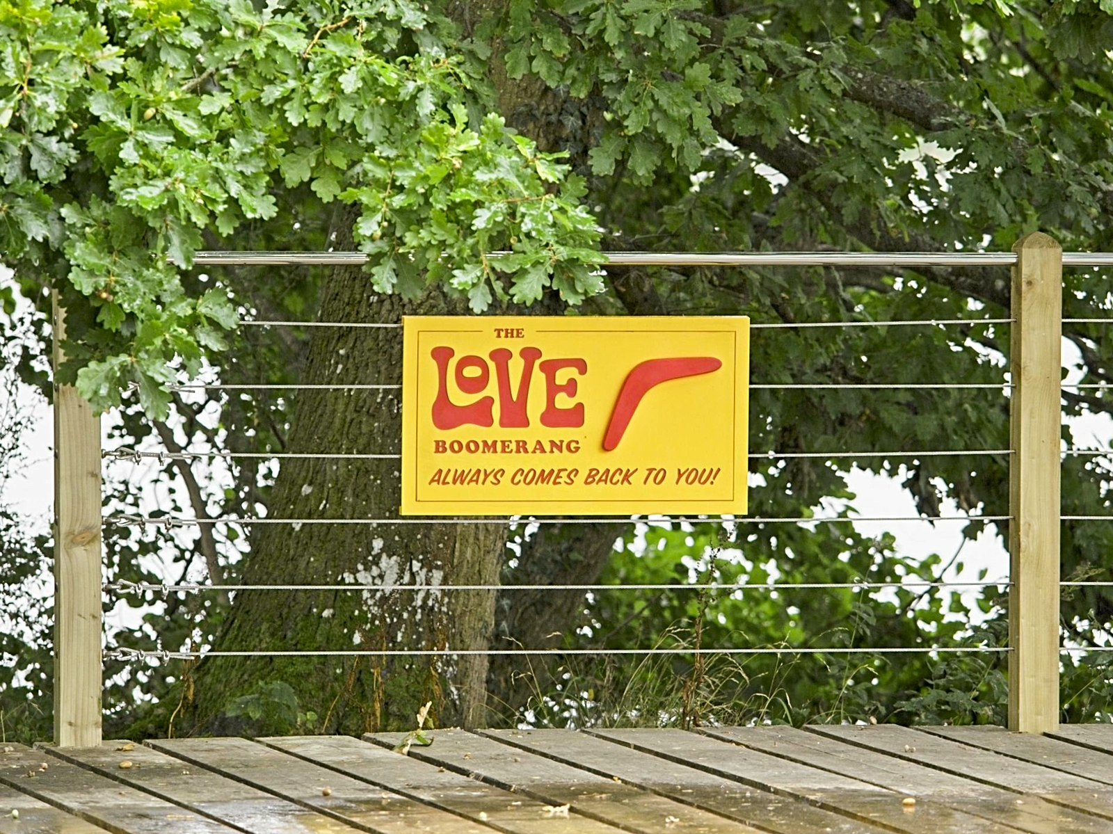 A wooden walkway with a wire and wooden fence along the side. Behind that are bushes and trees. On the wires lining the path is a yellow sign with red writing saying