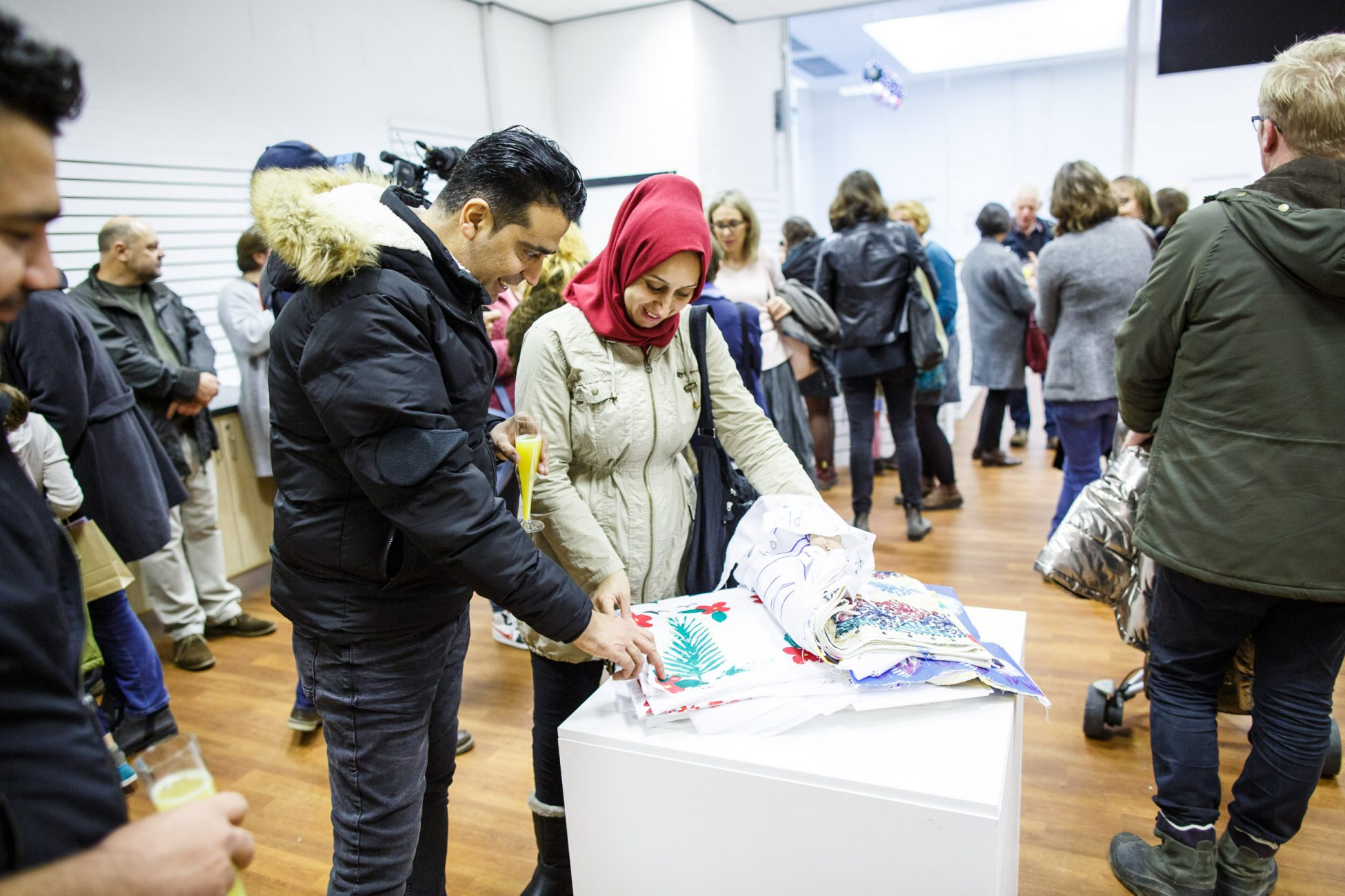 Photo in a gallery showing a book made up of colourfully decorated squares of fabric open on a plinth. A man in a black coat and jeans and a woman in a beige coat and red hijab are looking through the book and admiring the designs.