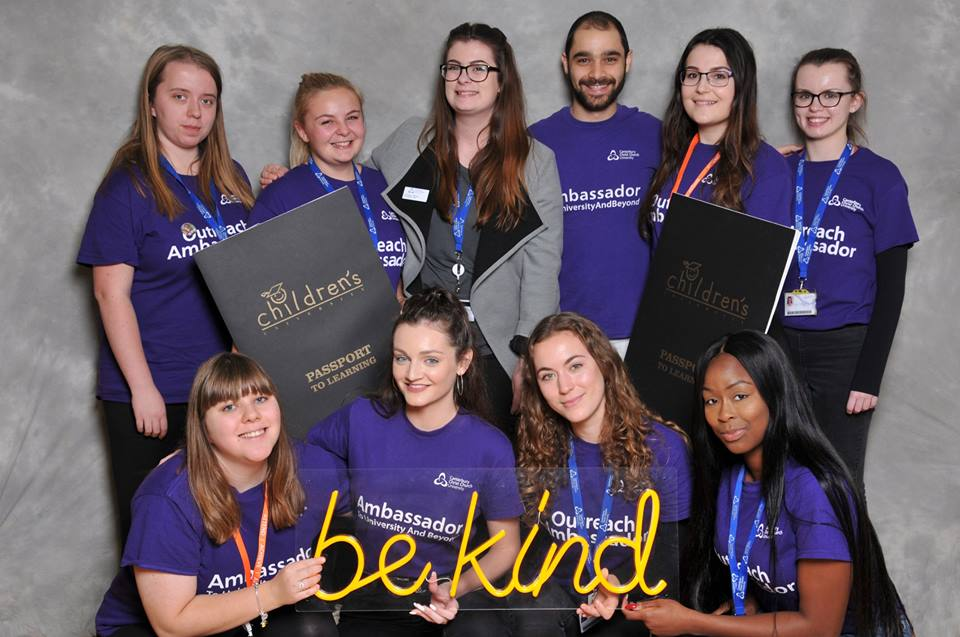 A group of ten young adults wearing purple t-shirts. Five women and a man stand at the back holding extra large black booklets that say Children's University, passport to learning on the front. Four females are crouched in front of them holding a yellow neon sign that reads be kind.
