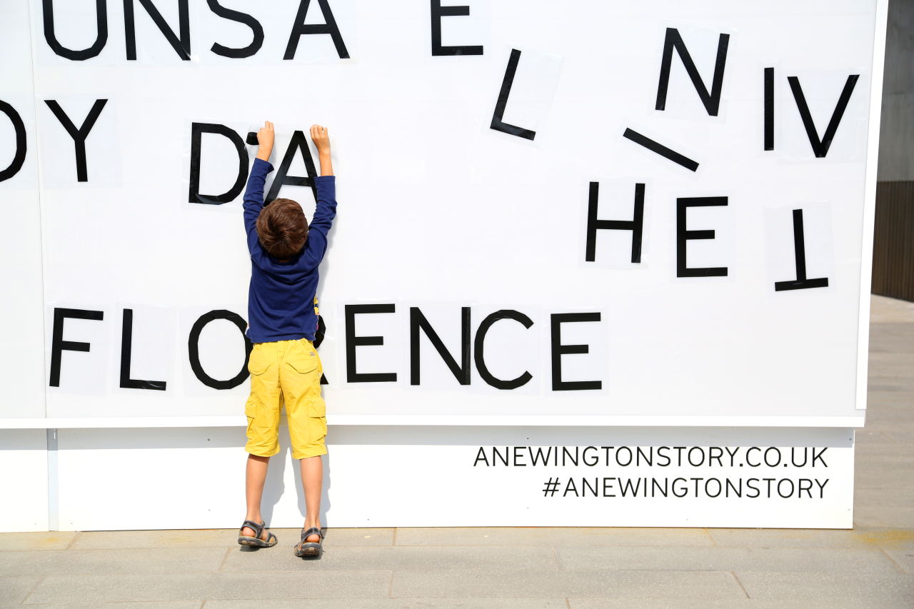 A photo of a young boy in yellow shorts reaches up. He is standing infront of a smooth white wall. There are large black moveable letters. The photo only shows part of the wall so now words can be read but there are about 12 letters partly visable. He is placing the letter 'a' in front of the letter d.