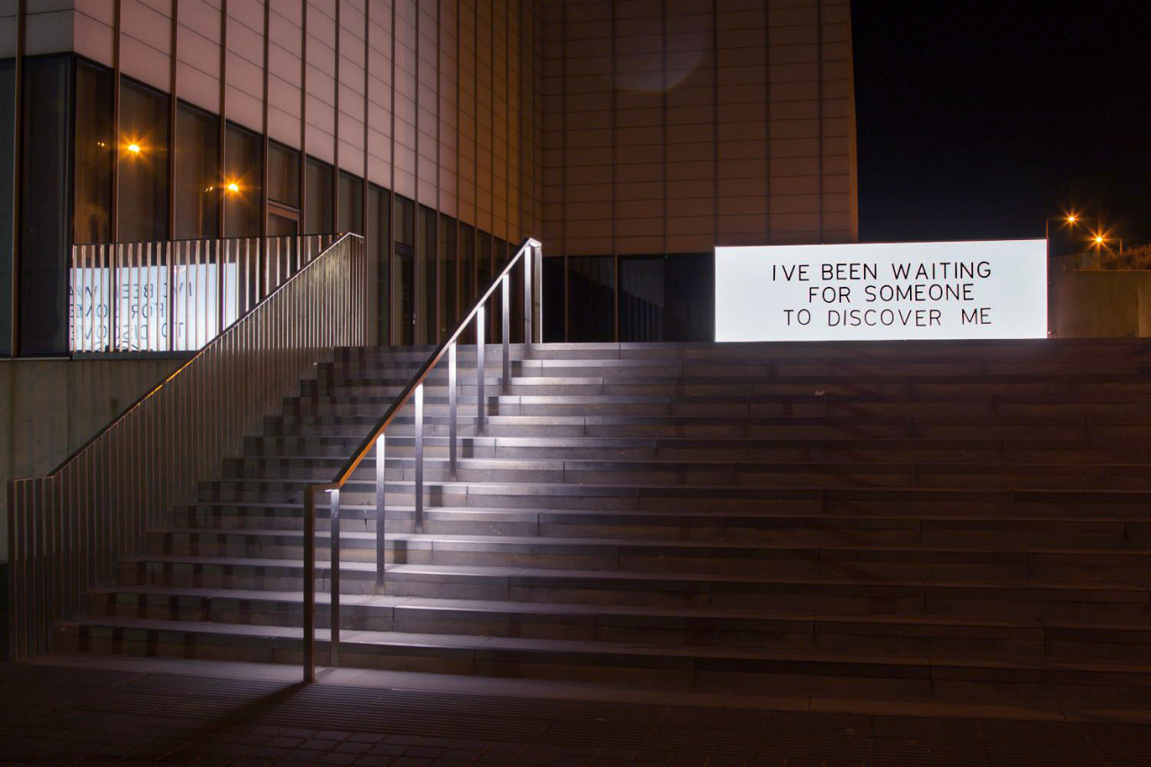 A photo taken at night-time outside a building with stairs in front. At the top of the stairs is a large white rectangular light board glowing. On the board in black capital letters it reads: I've been waiting for someone to discover me.