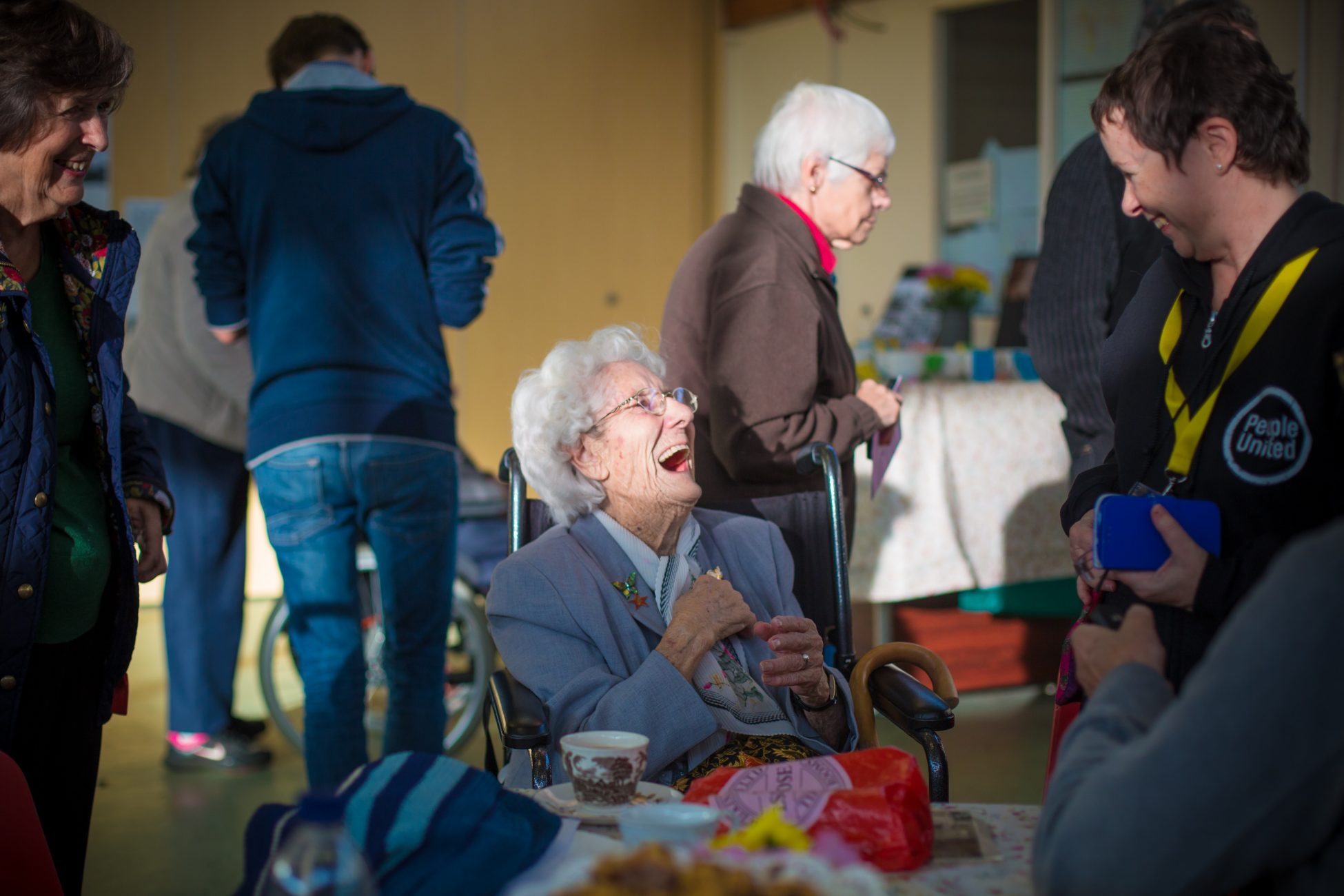 Photo of a hall or community centre with people milling about. In the foreground an older woman is sitting in a wheelchair next to a table with biscuits and an ornate cup and saucer. The woman is mid conversation with a woman who is standing next to the table and they're both laughing.