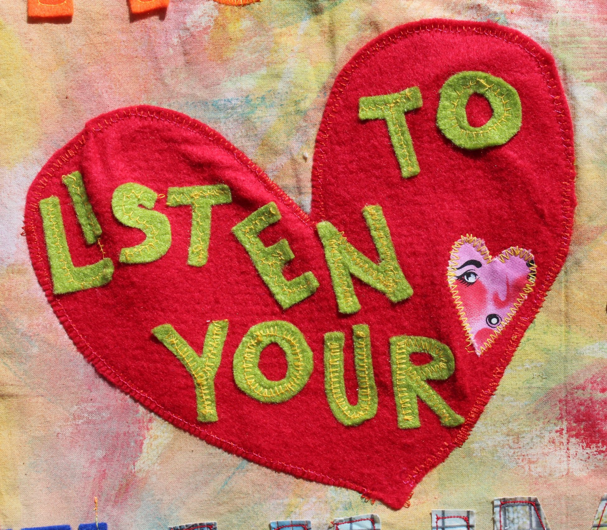 A red felt heart which has been stitched to the pastel painted fabric. On top of the heart are green felt letters spelling out