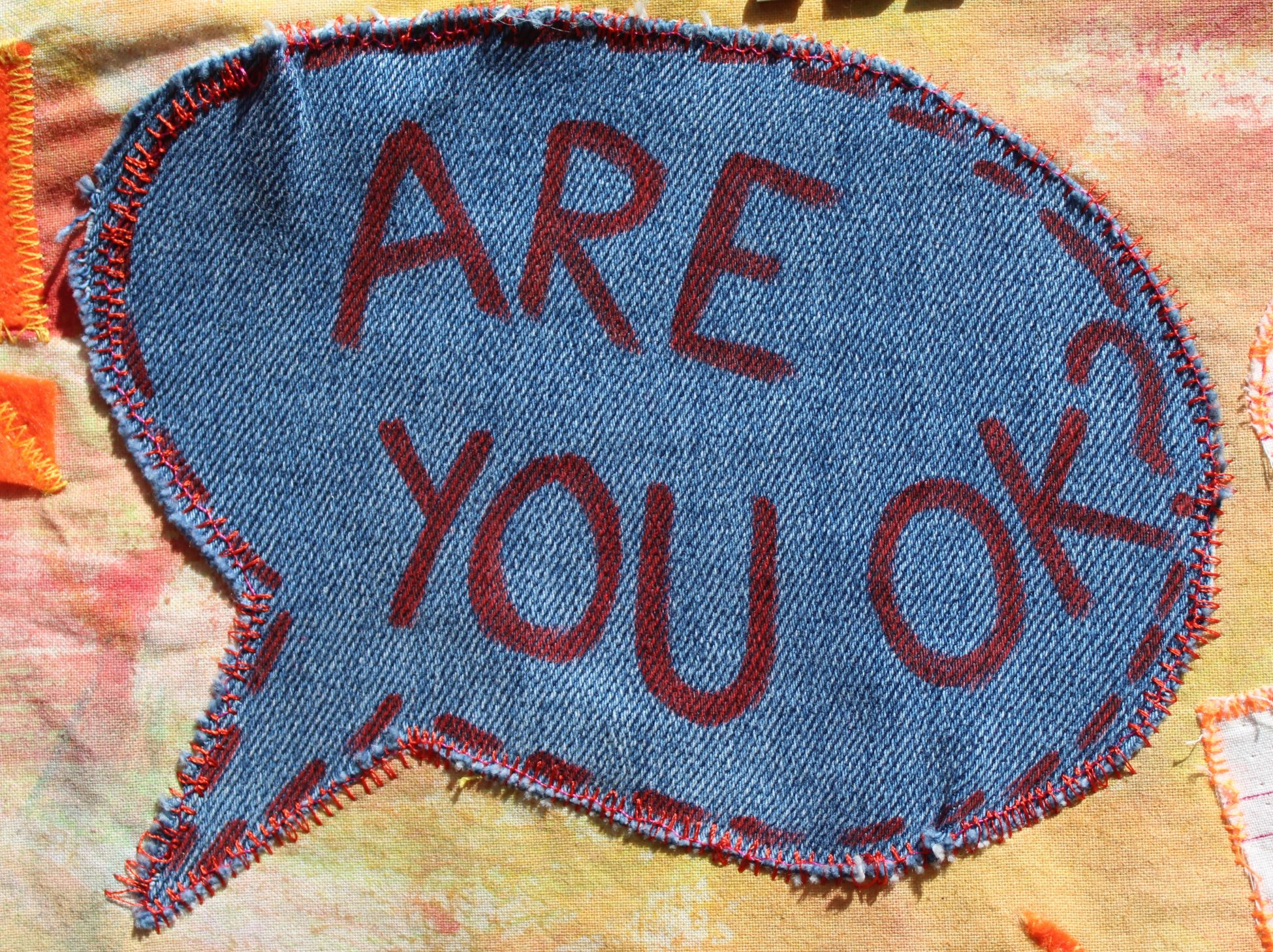 A patch of blue denim cut to the shape of a speech bubble with the phrase