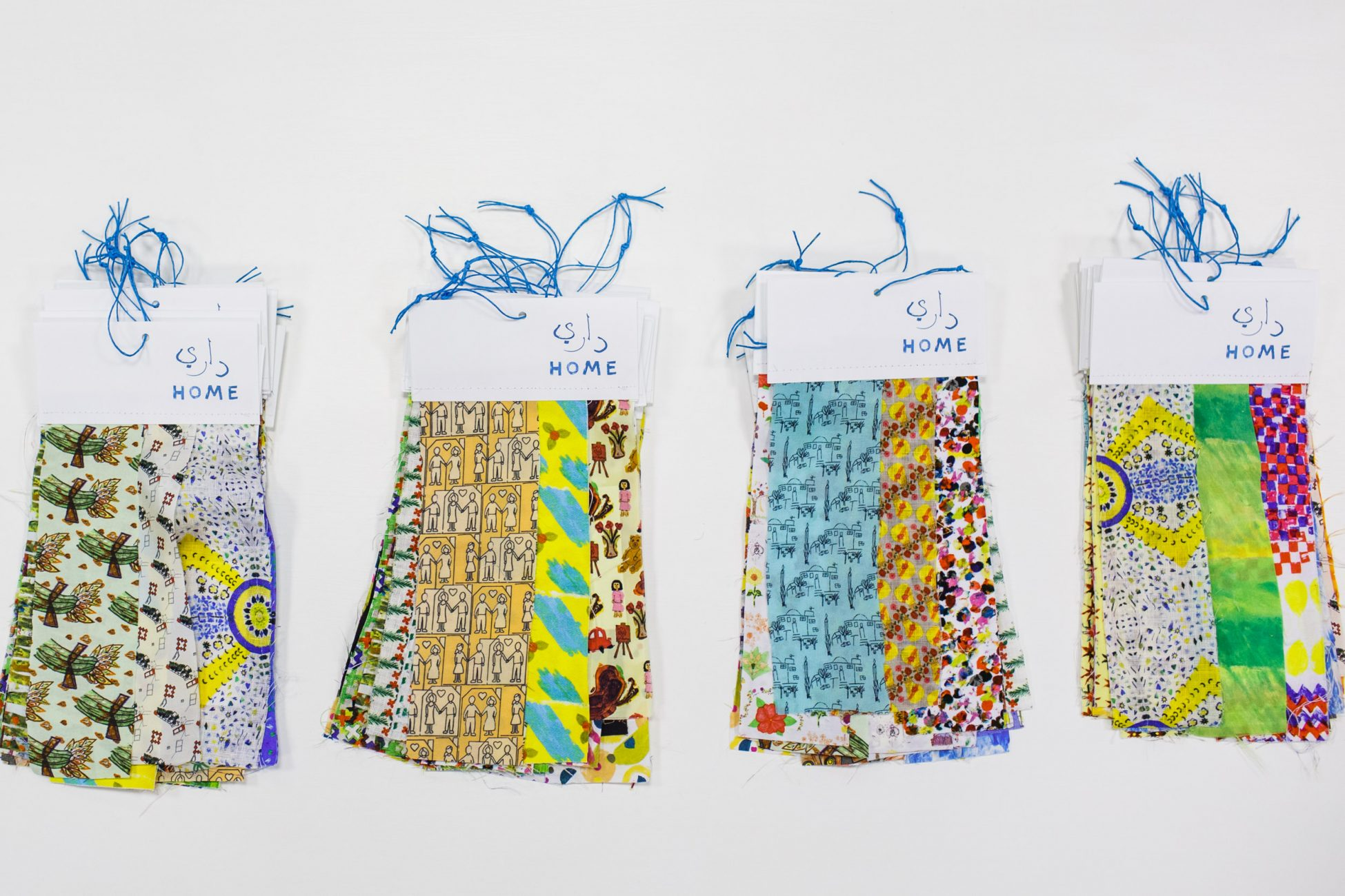 A photo of four piles of fabric strips that have been decorated with different colourful designs. Each set of fabric strips has a tag at the top saying HOME