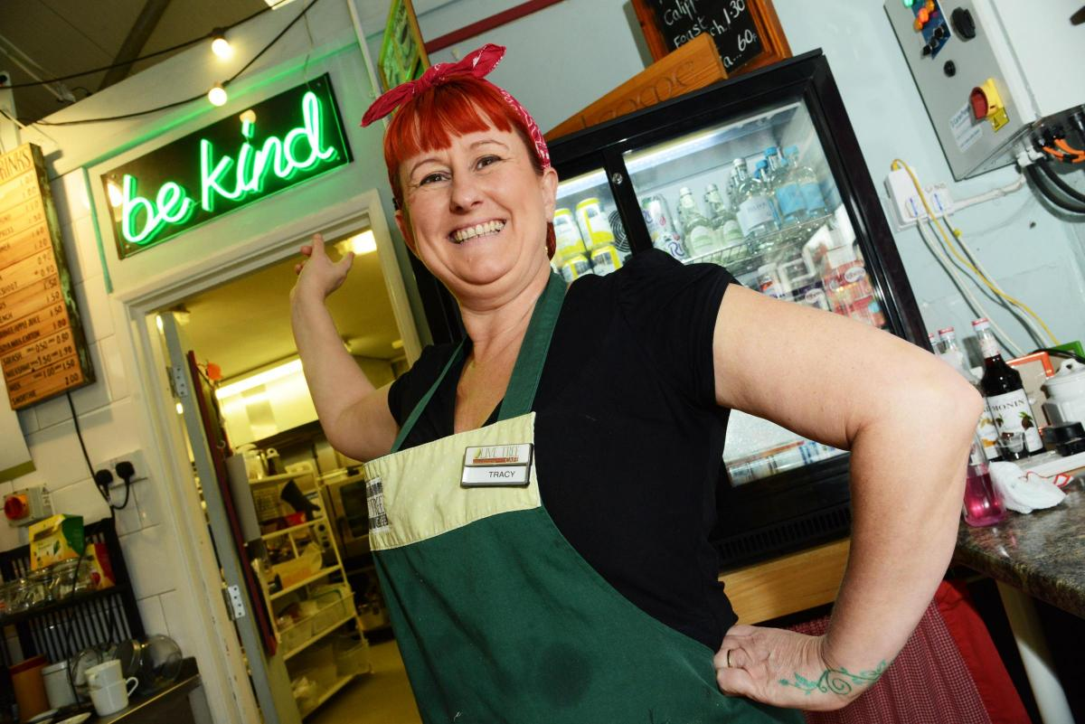 Photo of a woman in a cafe wearing an apron and name badge. She is smiling and pointing to a green neon sign above a doorway that spells out