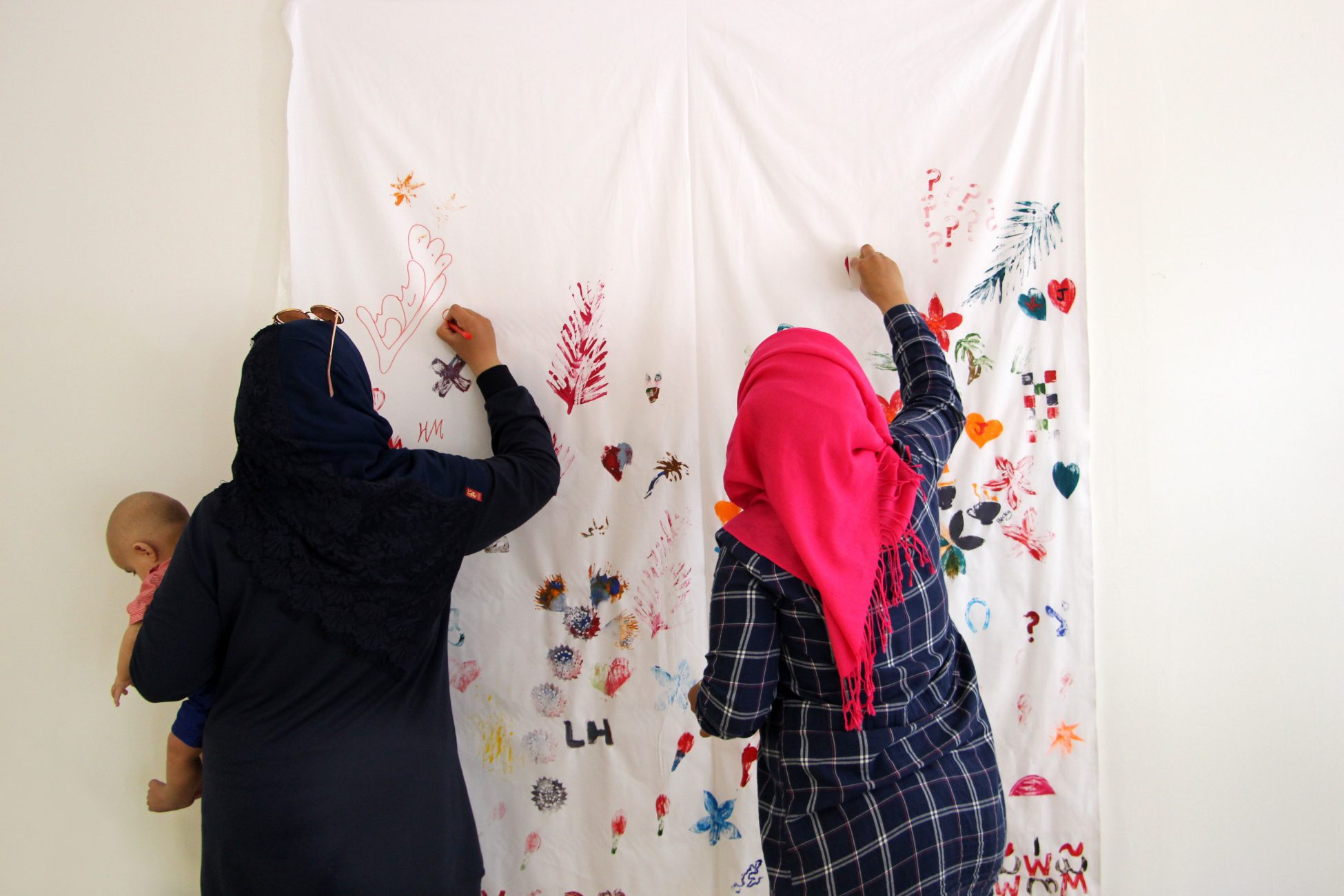 A photo of two women wearing hijabs facing away from the camera and decorating a piece of white fabric hanging up on a wall. One of the women is holding a baby in one arm.
