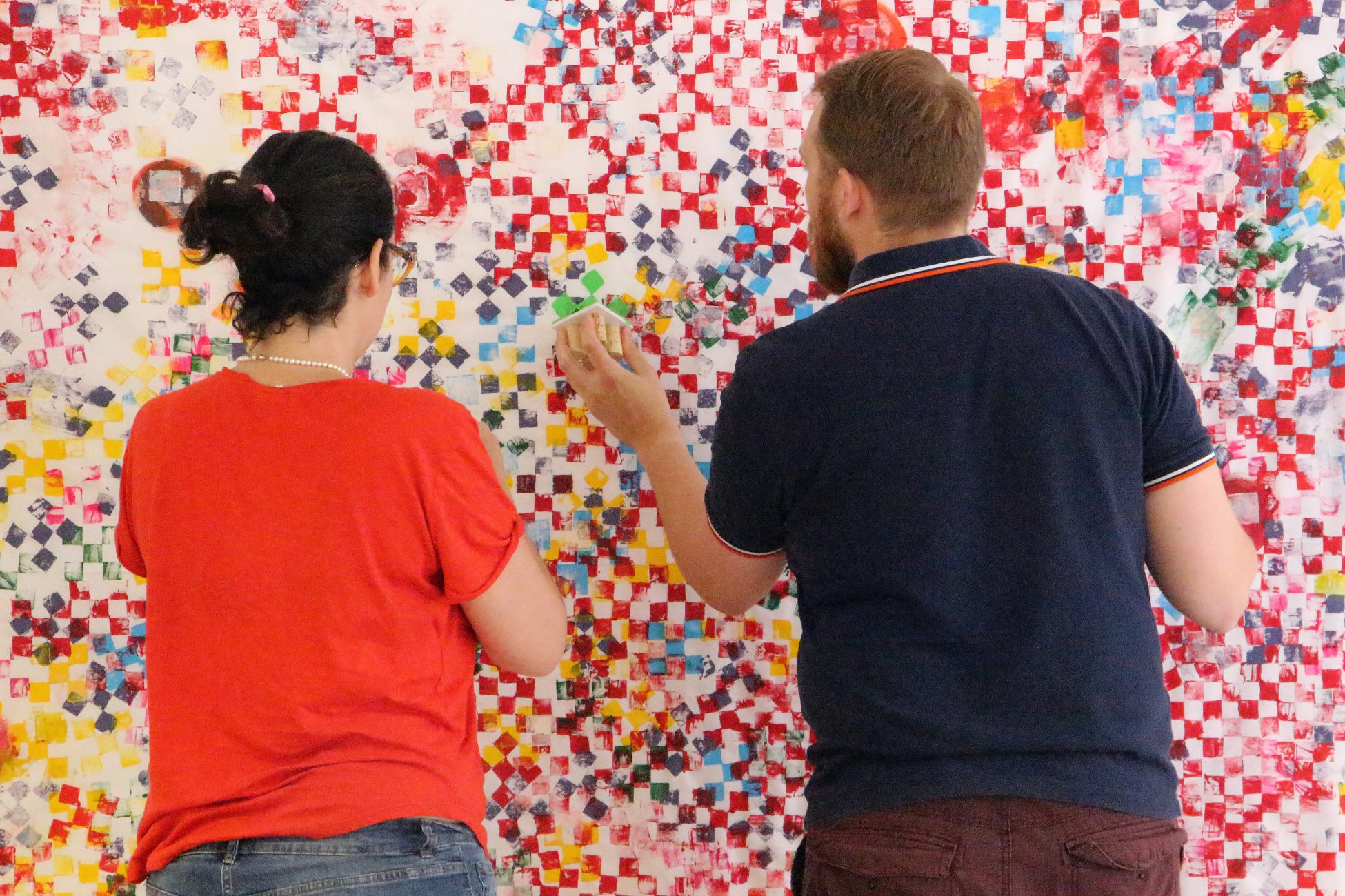 Photo of two people facing away from the camera and decorating a piece of white fabric hanging on the wall. One is using a stamp dipped in paint to stamp a pattern of colourful squares onto the fabric.