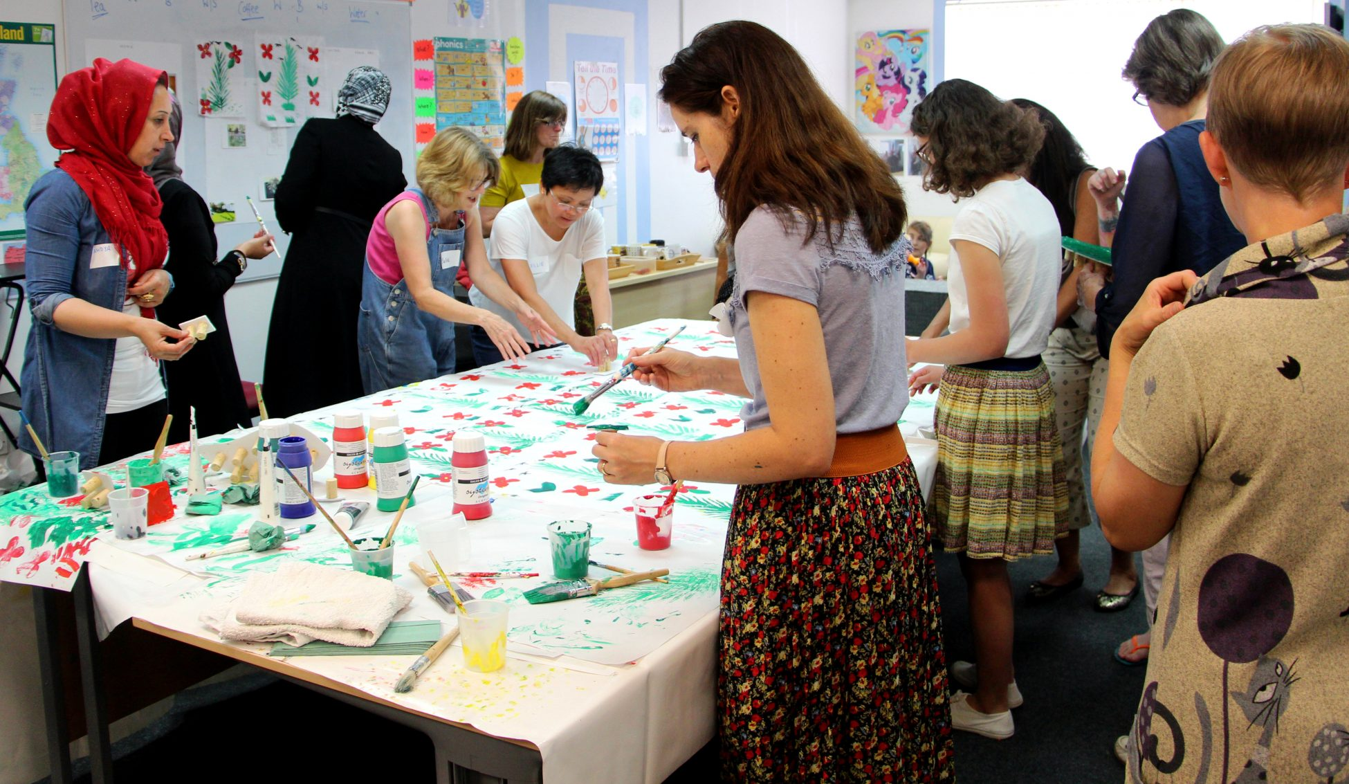 Photo of a group of about a dozen women grouped around a large table covered in white fabric. The women are painting designs onto the fabric.
