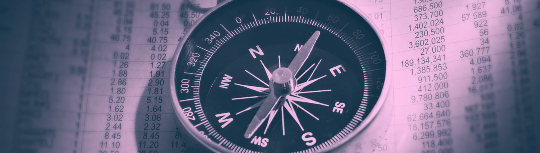 A photo of a compass on a printed out spreadsheet. The image has been altered to be blue and pink