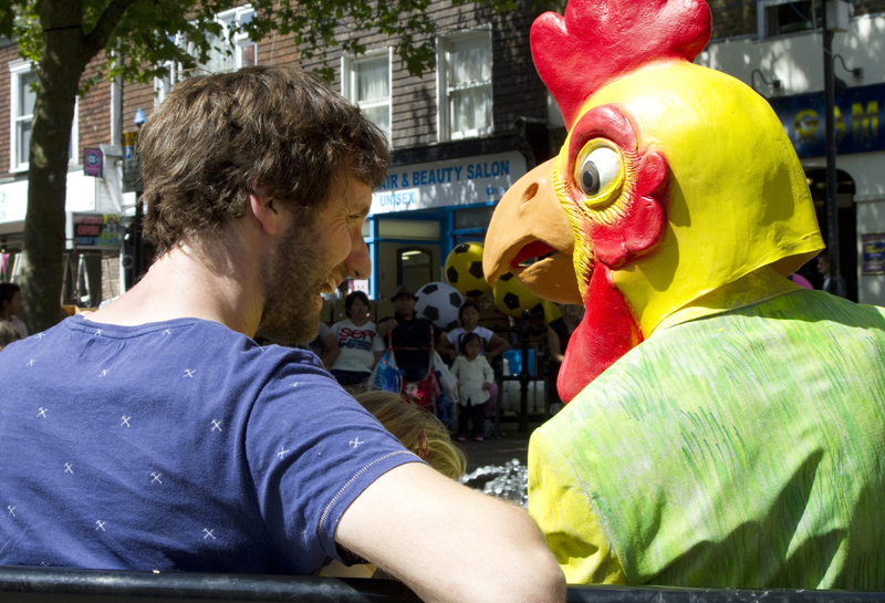 A man with a beard is laughing and sitting on a bench next to a person with a yellow rubber chicken mask on their head. The photo is taken on a high street and a small group of people can be seen in the background watching them.