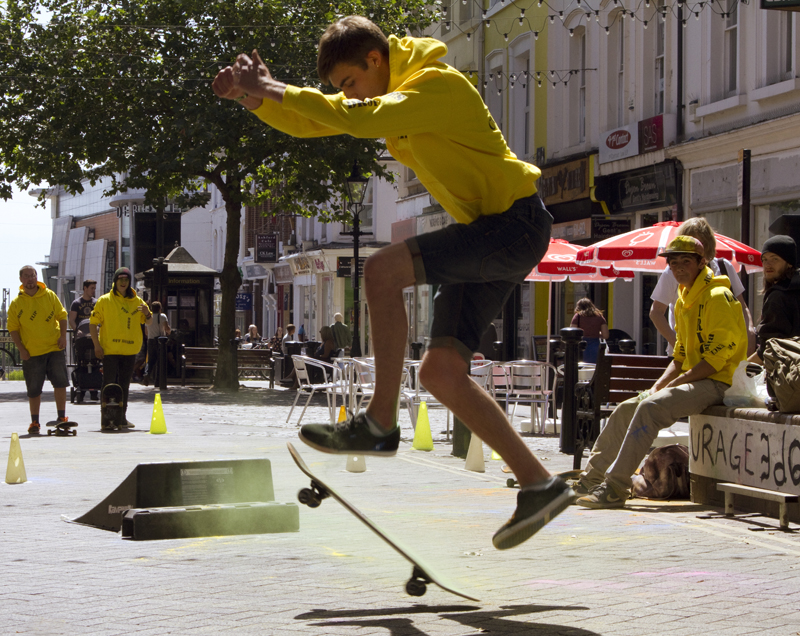 A male skateboarder on a high street is wearing a yellow hoody and jumping in the air.