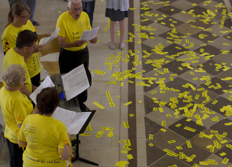 Five adults in yellow tshirts are holding pieces of white paper while singing. The floor has lots of large pieces of yellow confetti on the floor.