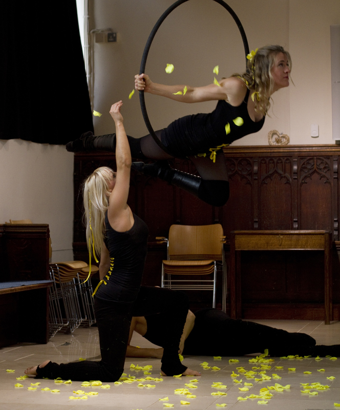 Two women dressed in black, one woman is kneeling on the floor with one arm in the air. The other is above her on a suspended black aerialists hoop. There is about 10 yellow feathers floating to the ground and about 50 feathers scattered on the floor.