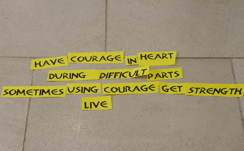 A grey tiled floor has pieces of yellow paper with one word on each piece laid out. In capital letters, the text reads: Have courage in heart during difficult parts sometimes using courage get strength live.