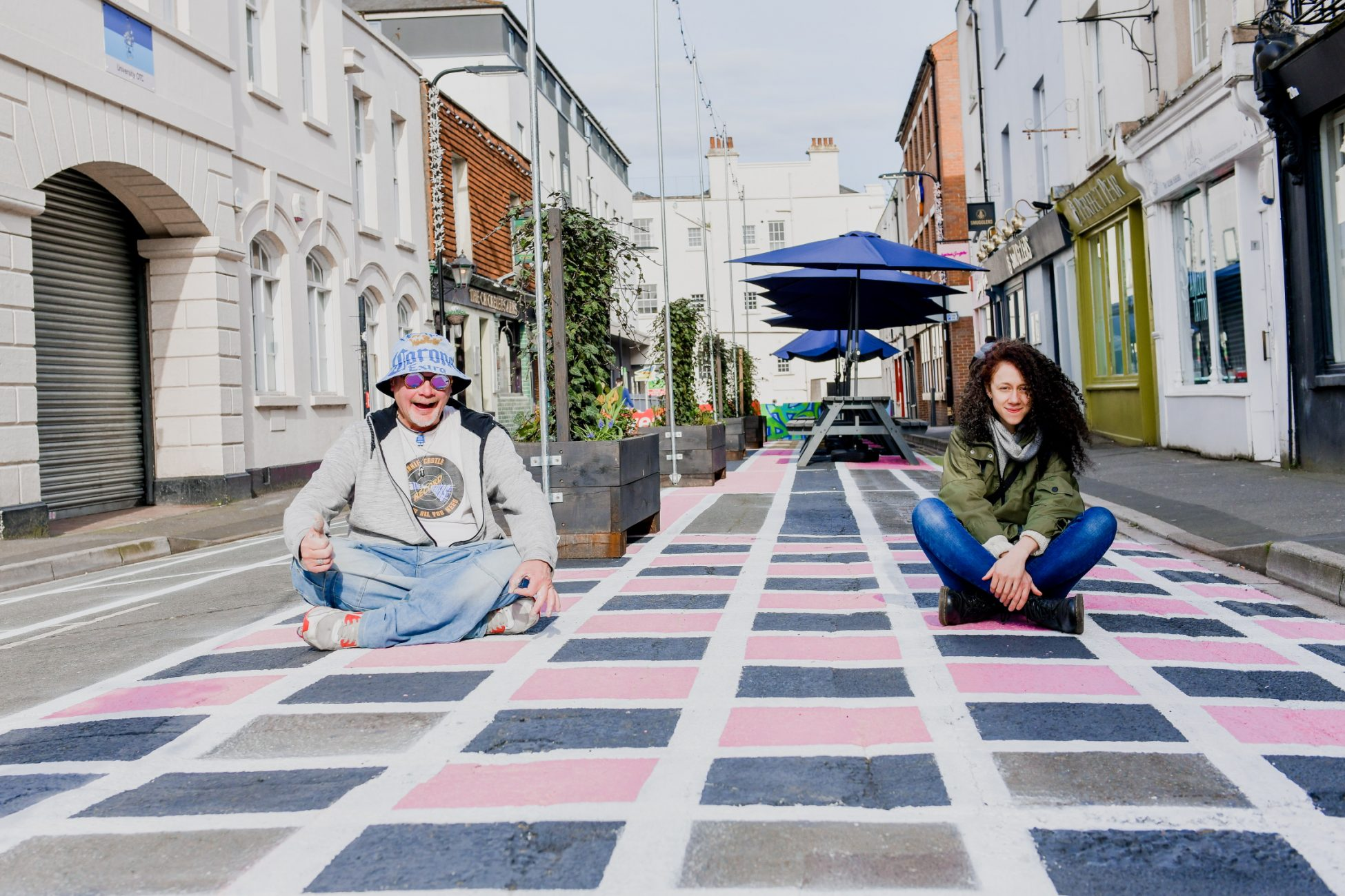 A photo looking straight down a commercial road with shops and businesses on either side. The road has been painted with a geometric grid in white, pink and blue. Sitting on the grid, cross legged are a white man in a hat, hoodie and jeans, and a white woman with brown curly hair, a green jacket and leggings. Behind them are large planter boxes with tall vines and plants, strings of fairy lights, and picnic benches with large blue umbrellas over them.