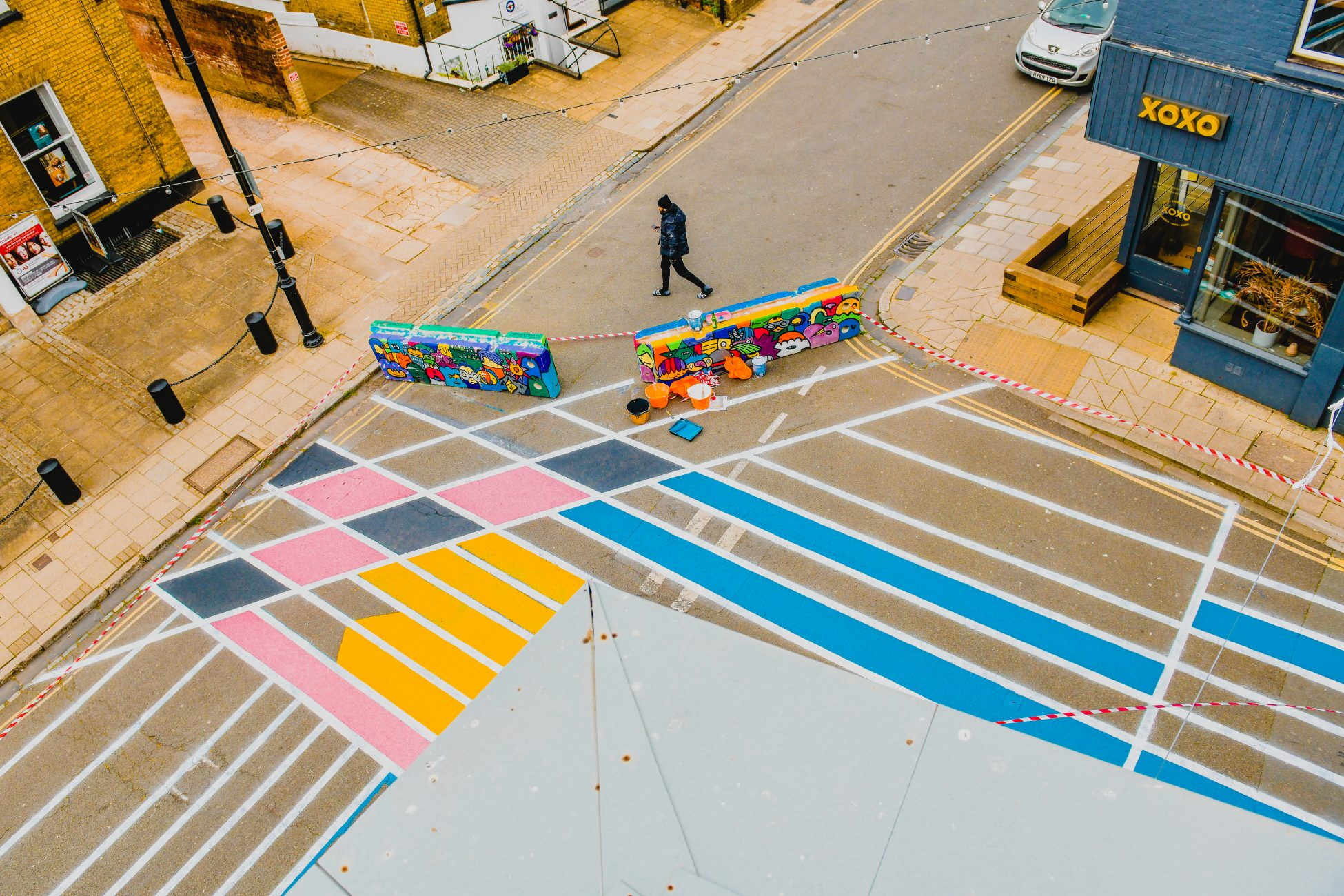 Photo looking down at a junction where two roads intersect. Large colourful boxes/crates have been placed across the junction blocking off two of the roads leading to the intersection. The blocked off roads have been painted with thick white lines running lengthways down the street, with a few more intersecting those lines. Some of the diamonds and rectangles this has created have been painted yellow, blue, pink and navy.