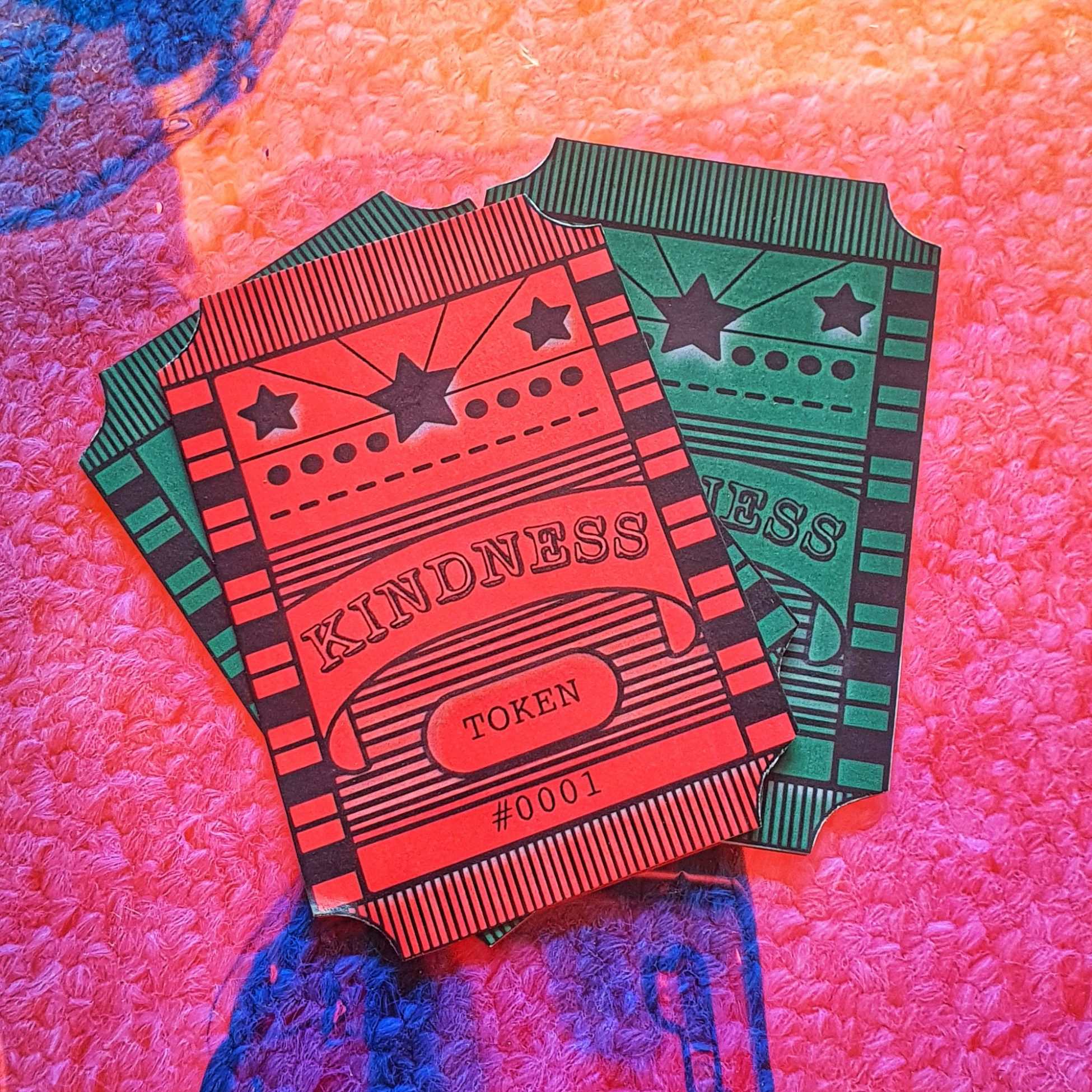 Three pieces of paper in the style of vintage arcade tokens are on a pink and blue textured background. There is one red token and two green tokens. They have the words 'Kindness Token #0001' and a design of stars and stripes in black.